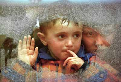 A ethnic Albanian boy peers through the window of a bus taking him with other refugees from the border town of Blace to a refugee camp 03 April 1999. Refugees forced out by Serbs from Kosovo continued to arrive today, joining an estimated 15,000 Kosovars, who have been waiting days for trains to take them across the border into Macedonia.