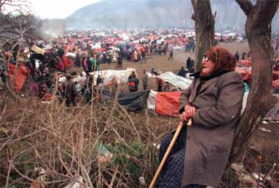 SKO08:YUGOSLAVIA-MACEDONIA-REFUGEES:BLACE,MACEDONIA,3APR99 - An elderly Kosovo refugee rests against a tree in a field where more than 25,000 ethnic Albanians are camping at the Yugoslav-Macedonian border April 3. More than 10 people died overnight in the camp due to the cold weather and lack of medicines.  yb/Photo by Yannis Behrakis   REUTERS